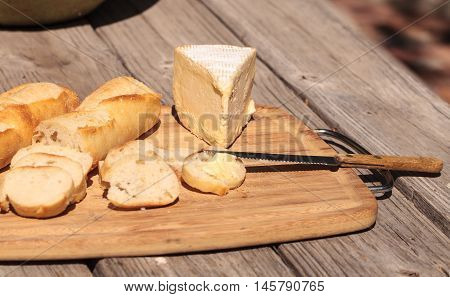 French bread and triple cream brie cheese on a cutting board with a knife.