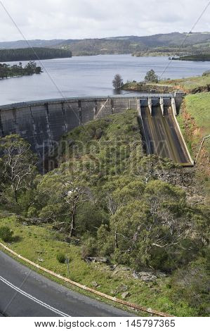 Concrete arch dam with ski-jump spillway of the Myponga Reservoir in Myponga South Australia. Includes the road leading to it in portrait orientation.