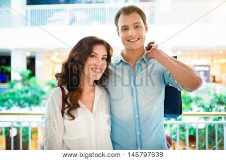 Young couple walking in a shopping mall and having fun