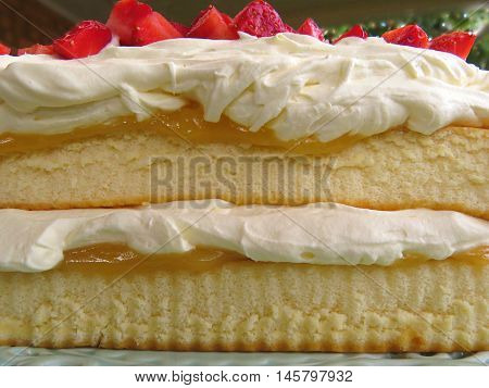 Sponge cake layers with cream, lemon curd strawberries