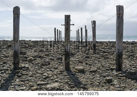 Low tide fully exposing the pylon pillar posts gradually decaying in the sunshine from the old jetty ruins at Myponga Beach South Australia.