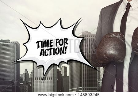 Time for action text on speech bubble with businessman wearing boxing gloves