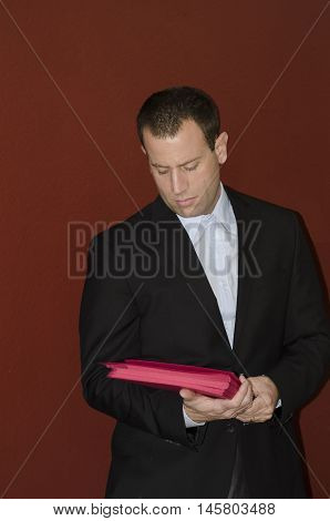 Business man in black suit with red file folders.