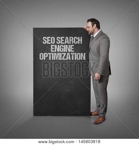 SEO search engine optimization text on blackboard with businessman standing side