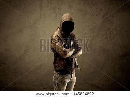 A suspicious faceless mature male in dark urban environment and light in front of a concrete empty wall background