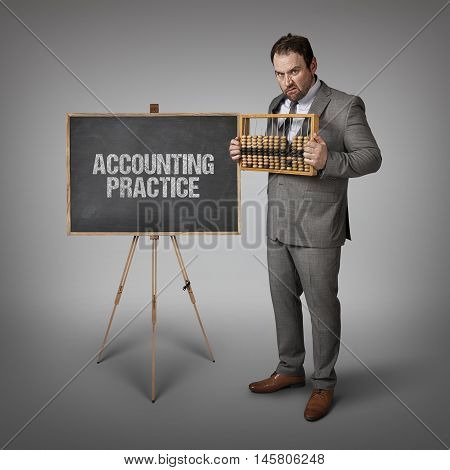 Accounting practice text on blackboard with businessman and abacus