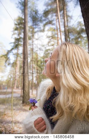 Young blond woman in white warm cardigan standing near an old tree and holding beautiful snowdrops in hands. First spring flowers in forest. Beginning of spring in a forest. Sunlight in a pine forest