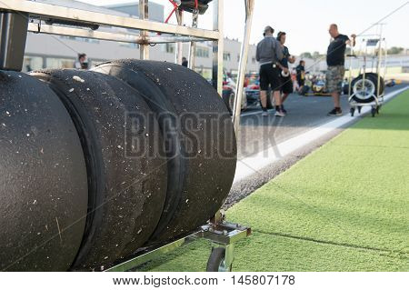 Black slick motor sport tire on trolley close up on race starting grid with out of focus background