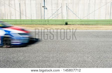 Blurred blue and red car nose racing on track during motorsport event coming into the image from left