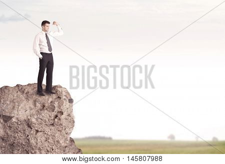 A successful good looking business person standing on top of a high cliff above country landscape with clear white sky concept