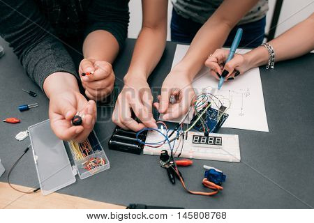 Collective electronics development with scheme. Breadboard and components with engineers hands on table, teamwork concept