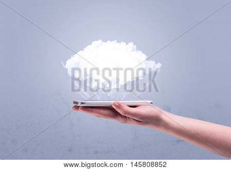 A male hand holding a mobile phone from profile view with an empty white cloud above the device for sales concept
