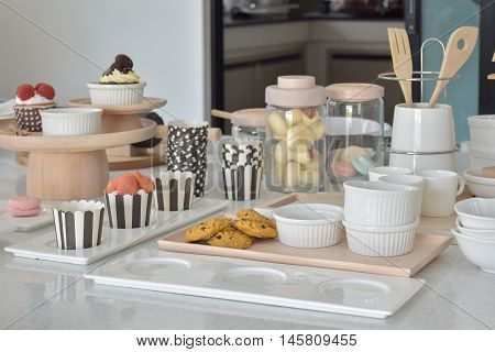 Cookies And Cupcakes With Cute Bakeware Setting On White Top Table