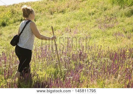 Woman traveler with a bag and relies on a cane
