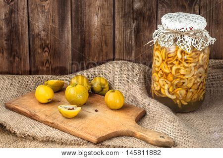 Homemade liquor, tincture from quince fruits. Autumn preserves on a wooden table