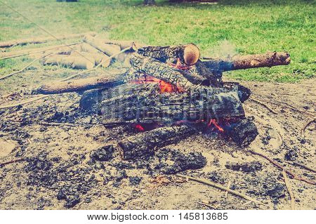 Rustic bonfire, on a camping place, vintage photo.