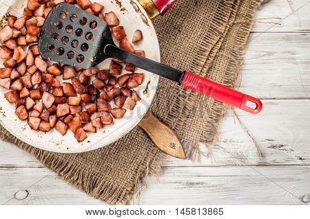 Fried sausages sliced in a cube on frying pan on wooden background. Cooking concept.