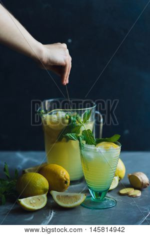 Lemonade drink with mint and ginger. Lemonade in the jug and glass with lemons and mint