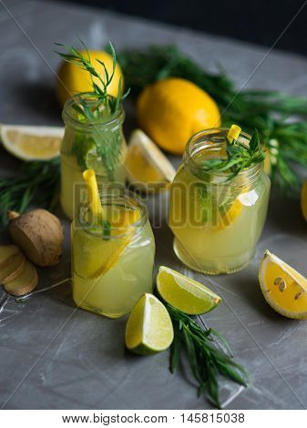 Lemonade drink. Lemonade in the glass jars with lemons, lime, ginger and estragon
