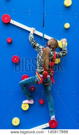 schoolgirl climbing the wall on ropes in entertainment center