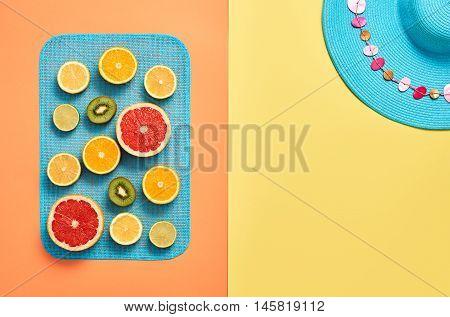 Fashion. Summer Beach Outfit. Fashion clothes Accessories Tropical Fruit Citrus, Orange, Grapefruit Lime, Kiwi. Stylish girl concept set. Fashion woman Hat. Bright Color. Creative Art. Minimal