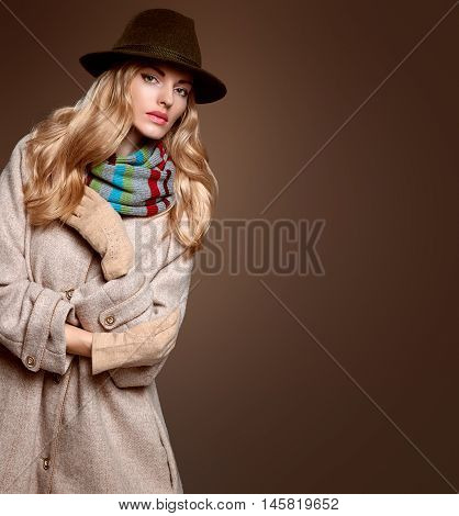 Fall Fashion. Model Woman in Autumn Fashion Outfit, Stylish Coat Trendy Hat, in Scarf, Gloves. Fashion Makeup. Playful Blonde girl with Wavy hair. Fall Autumn Winter. Fashion Pose. Creative Vintage