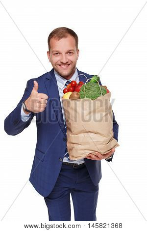 Handsome young businessman in suit holds shopping bag full of groceries isolated at white background. Healthy food shopping. Paper package with vegetables and fruits, happy male buyer shows thumb up