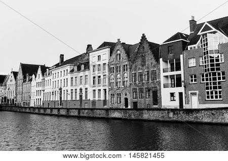 Bruges (Brugge), Belgium - February of 2016: Typical belgian street with traditional medieval houses and water canal, black and white