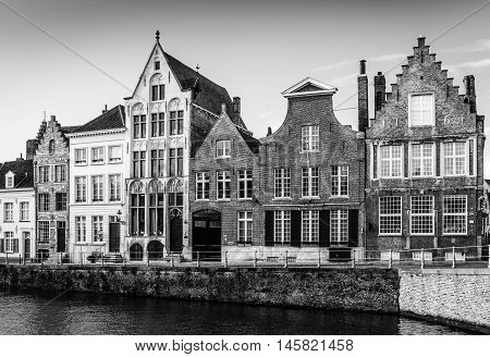 Bruges (Brugge), Belgium - February of 2016: Traditional belgian brick houses on the street of Bruges, black and white