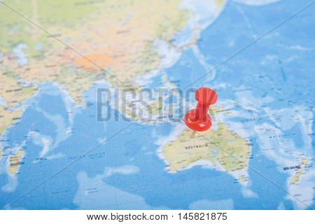 Closeup Red pushpin showing the location of destination point on a world map