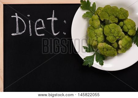 Boiled green broccoli on the plate with empty board for your text