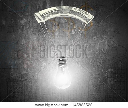 Bright light bulb with money parachute on doodles concrete wall background.