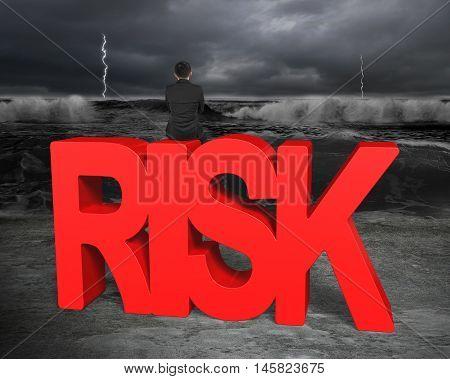 Man Sitting On Red Risk Word Facing Dark Storm Ocean