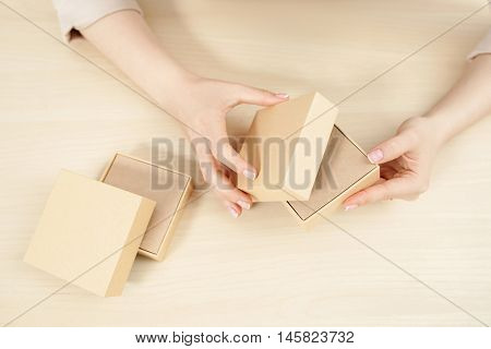 Female hands opening carton box, flat lay. Top view on woman holding and unblocking package with some product, free space. Delivery service. online shopping, parcel getting concept