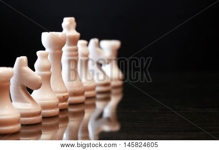 Set of chess pieces made from Onyx against dark background