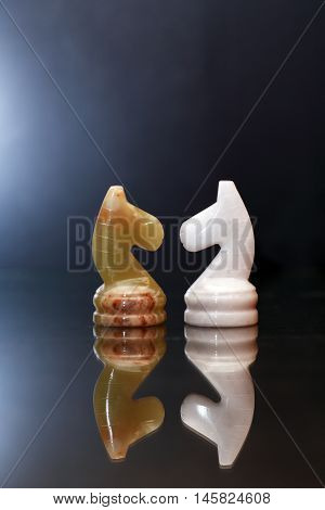 Opposition concept. Two chess horses made from Onyx against dark background