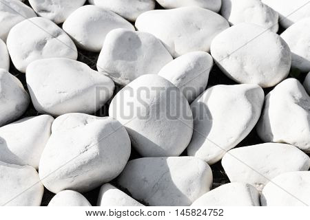 Background texture of smooth white stones or rocks used in landscaping and construction for decoration in a close up full frame view