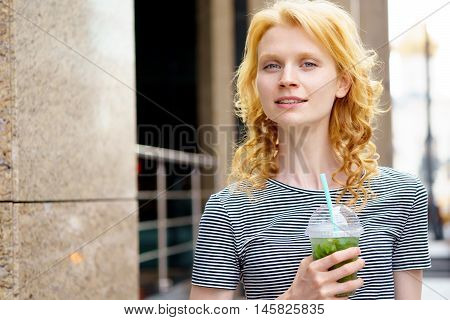 Portrait of stylish young blond woman walking and drinking tasty fresh drink mojito on hot summer day