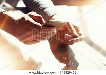 Closeup Man Holding Hand Credit Card.Businessman Use Smartphone Online Payments Shopping.Guy Touching Screen Mobile Phone Name Numbers Plastic Debit Kard Holder.Flares, Blurred Background
