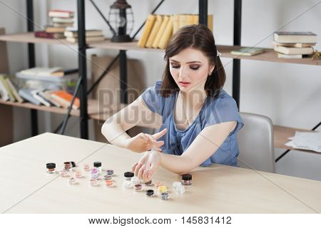 Woman trying eyeshadow colours on her hand. Make-up artist testing colors of decorative cosmetics. Beauty blogger doing swatches