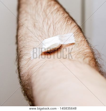 Close-up detail of man hand with adhesive tape after blood transfusion