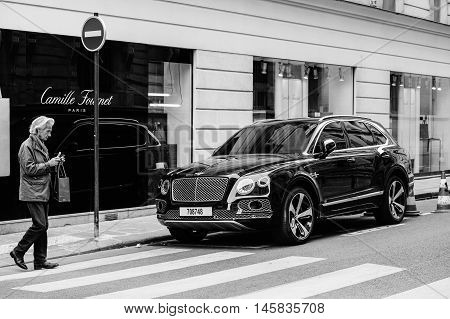 PARIS FRANCE - MAY 21 2016: Black and white of man taking photo of the luxury Bentley Bentayga Hybrid SUV on the streets of Paris France- street fastion