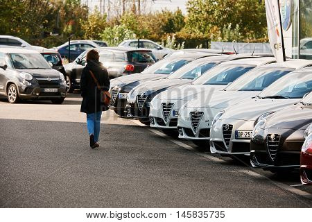 PARIS FRANCE - OCT 10 2015: Woman walking between rows of new car to choose the most precious one at the Alfa Romeo car store