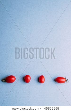 Four Cherry Tomatoes On A Blue Background, Space For Text