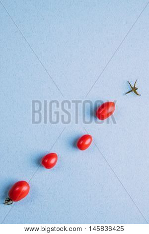 Four Red Cherry Tomatoes On A Blue Background