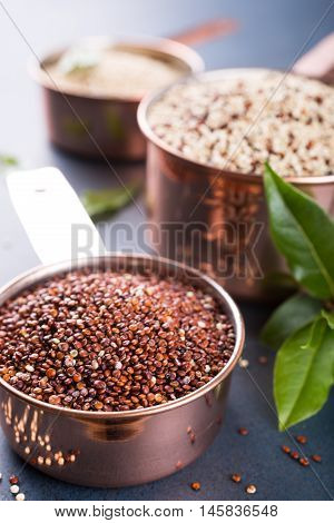 Stack of three Mixed raw quinoa, South American grain, in copper measuring cups with bay laurel leaves on blue background. Healthy and gluten free food.