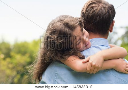 Small pretty girl embracing her father outdoor. Portrait of lovely daughter hugging her dad at park. Young father holding beautiful daughter at garden.