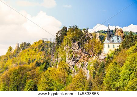 Ruins of Vranov Castle with small rock chapel, aka Pantheon, in Mala Skala on sunny summer day with blue sky and lush green trees, Bohemian Paradise, aka Cesky Raj, Czech Republic