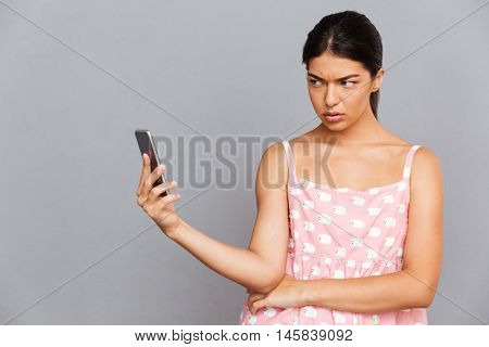 Portrait of a displeased brunette woman in pink dress making selfie photo on smartphone isolated on a gray background