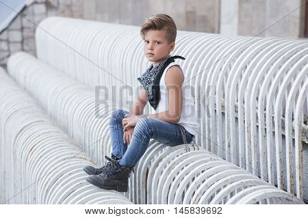 Stylish little boy sitting with a serious expression . It is very stylish . Children's emotions